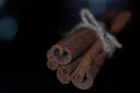 macro photo of sticks of cinnamon reknitted twine against a dark background フォト