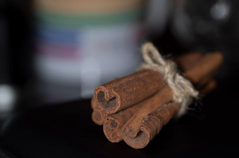 Macro photography of sticks of cinnamon reknitted by twine against a dark Photo
