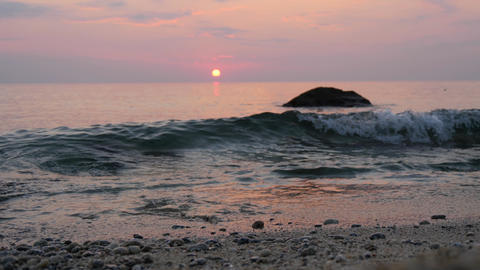 Pink sunset sky over the sea. Waves roll on sand and pebbles on a coast Footage