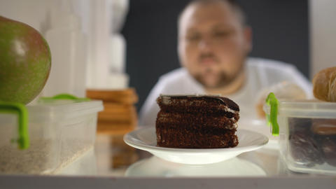 Oversize man taking piece of cake from fridge at night, diabetes risk, calories Footage