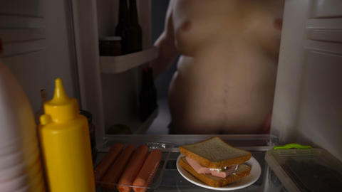 Fat male taking sandwich from fridge, unhealthy nutrition, sedentary lifestyle Live Action