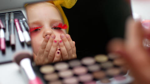 A beautiful little girl at the mirror makes herself a make-up Footage