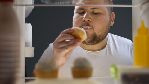 Overweight man opening fridge and eating delicious cream cake at night, dieting Live Action
