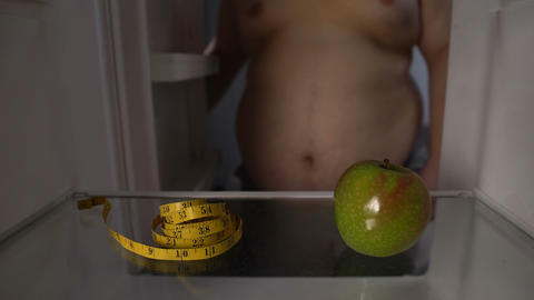 Green apple and measuring tape in fat mans fridge, healthy nutrition concept Live Action