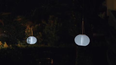 Round white paper lanterns in night garden Live Action
