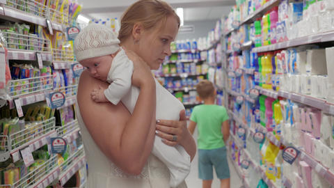 Mum with baby buying things in household goods section of supermarket Footage
