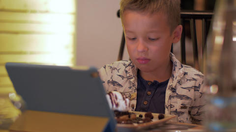 Child having meal and watching touch pad in cafe Footage