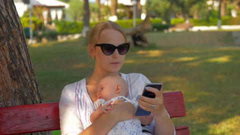 Woman using mobile during outing with baby in the park 영상물
