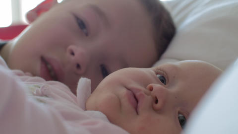 A boy kissing his baby sister on the cheek Footage