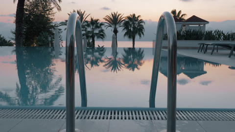Steadicam shot of an empty swimming pool and the evening scenery Live Action