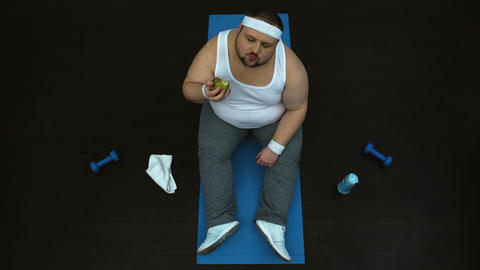 Hungry fat man eating green apple after gym workout, healthy nutrition, top view Live Action