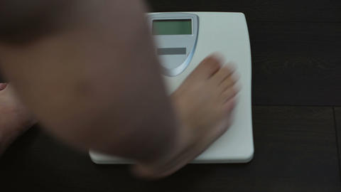 Fat male legs on scales, everyday weight measuring, sedentary lifestyle, obesity Footage