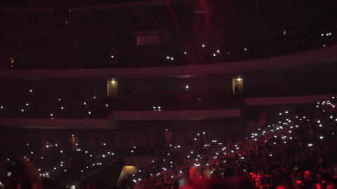 Fans at concert waving lanterns in the dark Live Action