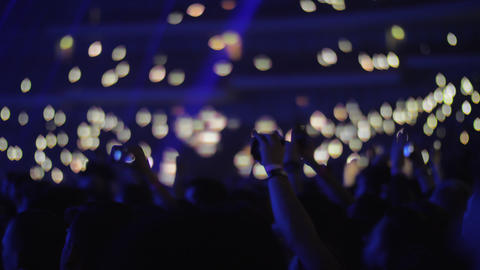 Crowd of music fans with lights in dark concert hall Live Action