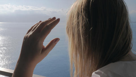 A woman on a balcony talking to a phone and a sea view behind her Footage