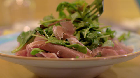 Green salad with prosciutto as appetizer at the restaurant Footage