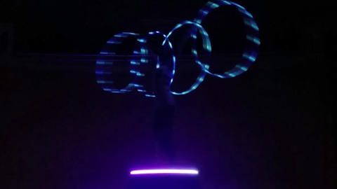 The girl in white costume twists four hulahoops with led lamps inside. Making Footage
