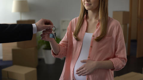 Male agent hand giving key from house to young pregnant woman affordable housing Footage