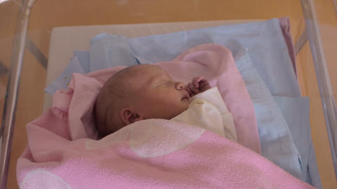 A newborn baby girl sleeping in a moving hospital baby cart Footage