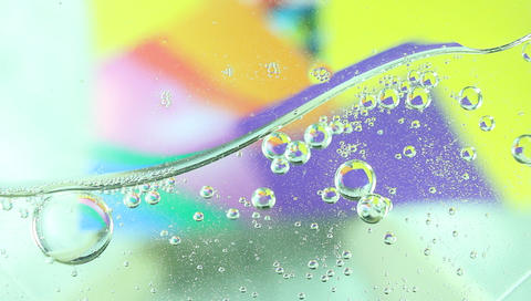 abstraction of droplets of machine oil on a glass top on a colored blurry Archivo