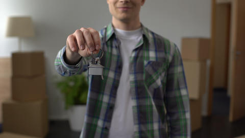 Man showing key from apartment, affordable lending, investment in real estate Live Action
