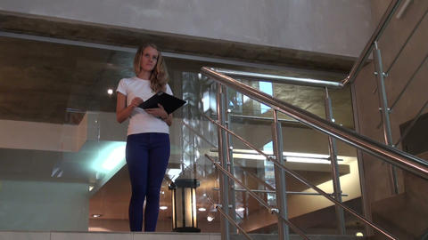 The girl on the stairs in the business centre Stock Video Footage
