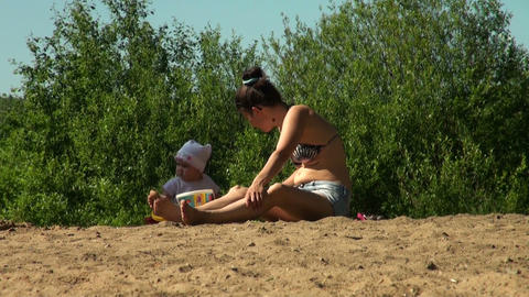 Mother and daughter sunbathe on the sand Stock Video Footage