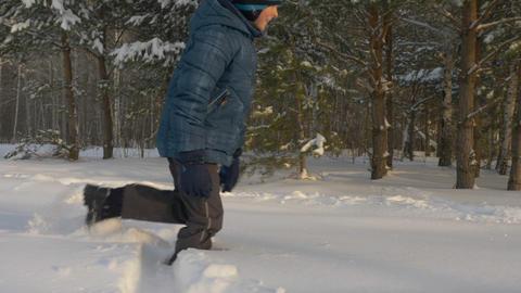 Happy boy teenager walking through snowdrift in winter forest. Winter activity Live Action