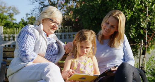 Multi-generation family looking at photo album in garden 4k Live Action