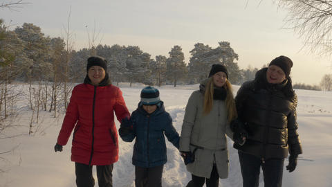 Friendly family walking in snowy forest at sunny winter day. Winter activity Footage