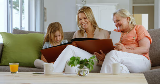 Multi-generation family looking at photo album in living room 4k Live Action