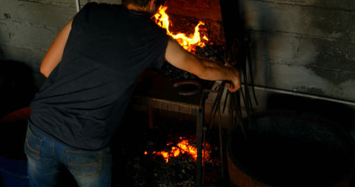 Metalsmith heating horseshoe in fire 4k Live Action