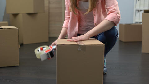 Lady from moving service carefully packing boxes with stuff and carrying out Footage