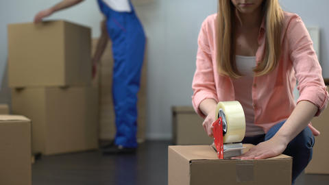 Lady packing things in box, moving company worker carrying baggage, moving out Live Action