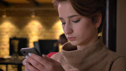 Close-up portrait of young short-haired woman attentively watching into Footage