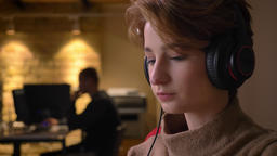 Close-up portrait of young short-haired woman putting off her headphones and Footage