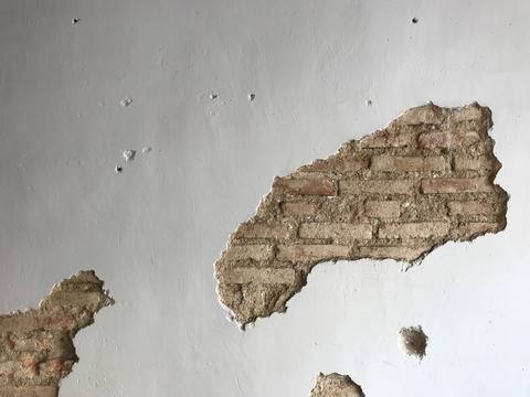 designed antique white cement wall with cracked space which shows old brick Photo