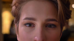 Close-up eye-portrait of young attractive short-haired woman calmly watching Footage
