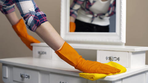 Housekeeper in rubber gloves dusting the surfaces in the room with special Footage