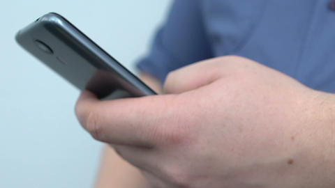 Male hand typing message on smartphone, lazy break time, sedentary lifestyle Footage