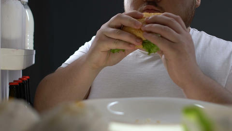 Addicted to junk food man chewing hamburger in front…, Live Action