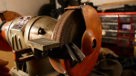 craftsman uses an electric wheel to grind a metal rod in his home workshop Footage
