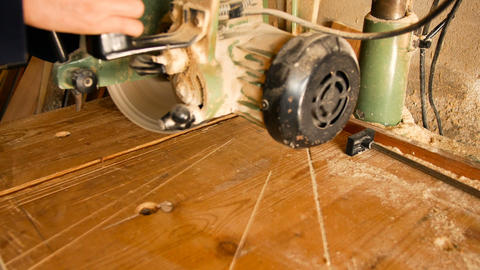 craftsman uses a circular saw to make a cut to a piece of rough wood in his home Archivo