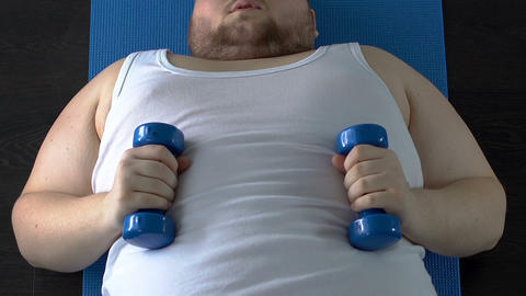 Weak muscles fat man lifting dumbbells up with effort lying on floor, fitness Footage