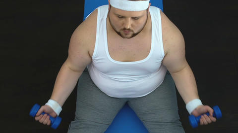Sport chubby man lifting dumbbells and showing success gesture after workout Live Action