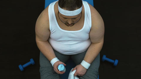 Tired obese man wiping sweat with towel and drinking water after sport workout Live Action