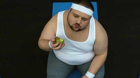 Chubby man biting green apple with pleasure, healthy nutrition habit, dieting Live Action