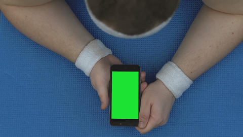 Sportsman watching online fitness video, lying smartphone on mat, workout break Live Action
