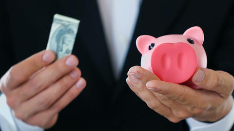 Business man putting money in piggy bank, rich investor making contribution Live Action