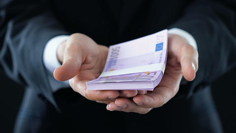 Man in suit receiving bunch of euro money, cash in hands close-up, financial aid Live Action